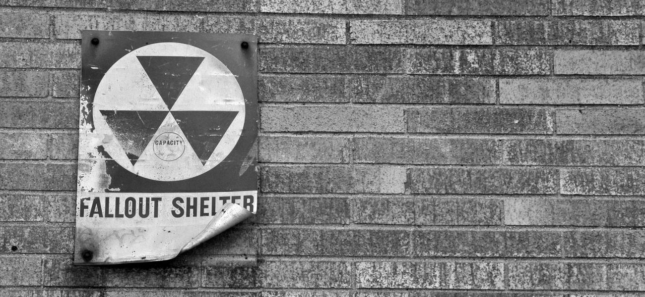 Black and white fallout shelter sign on brick wall.