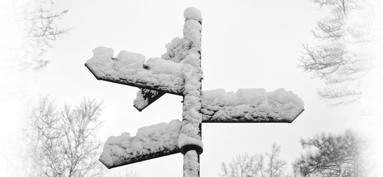 Snow-covered signposts pointing in different directions.