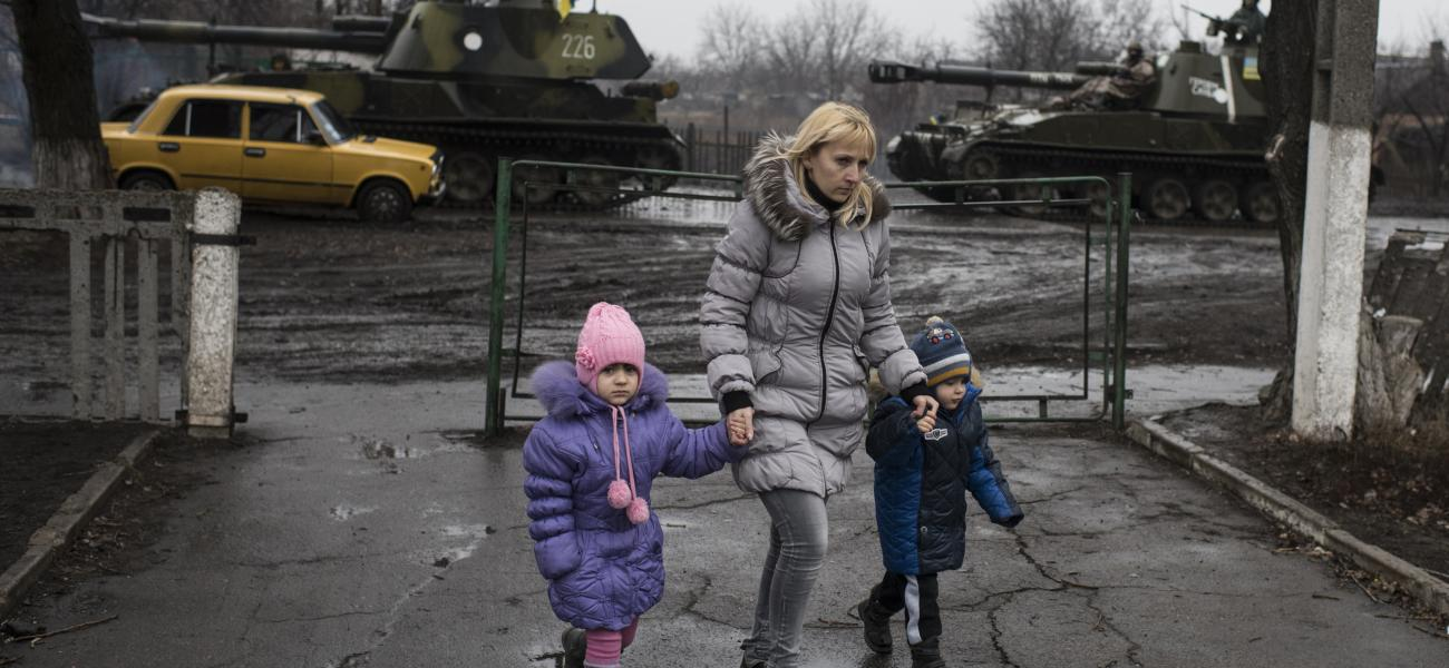 Eastern Ukraine, March 2015: A woman walking with two small children.