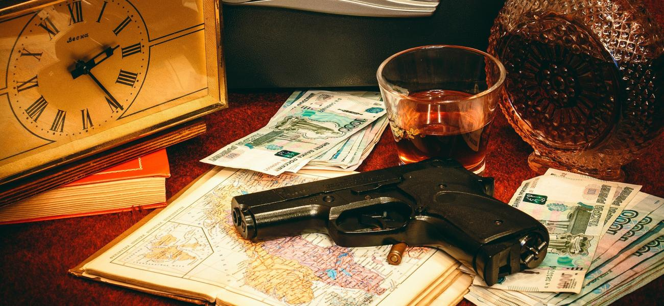 Gun and bullet on a map next to ruble bills.