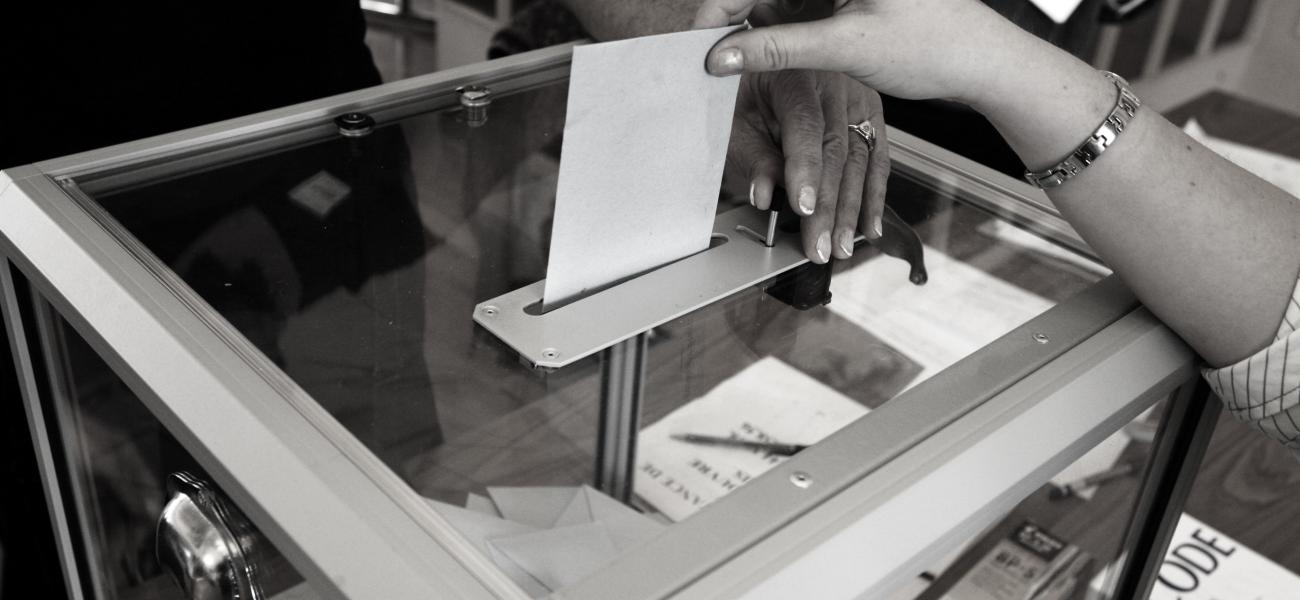 Hand dropping ballot in ballot box.