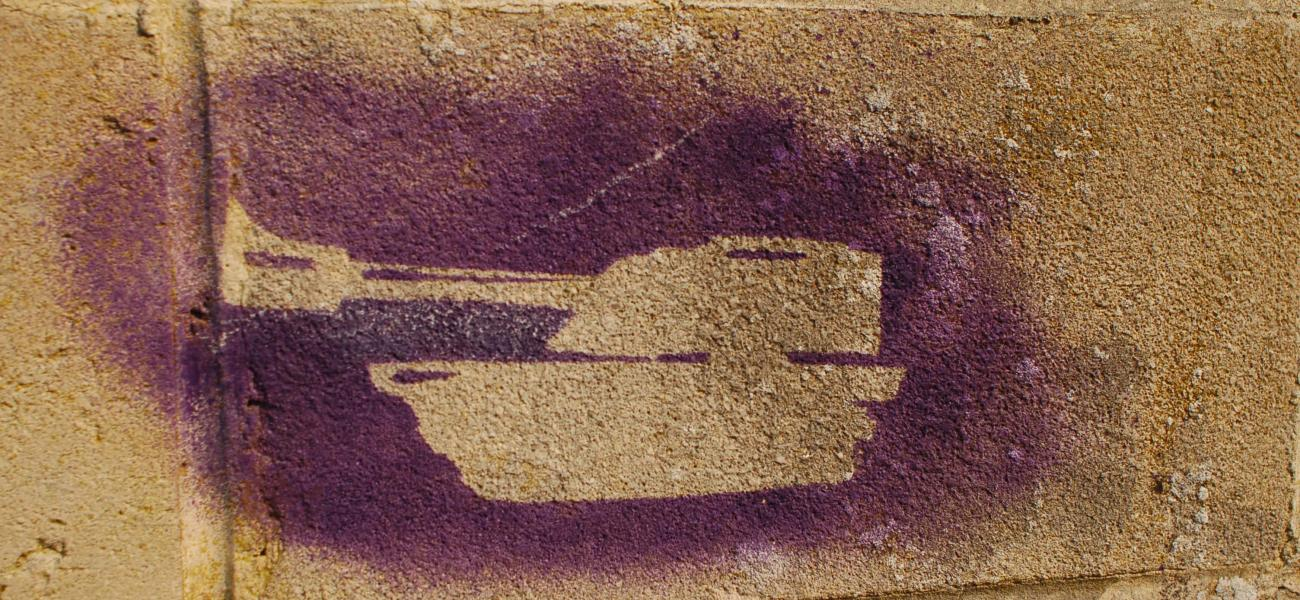 Tank silhouette spray-painted on a brick wall.