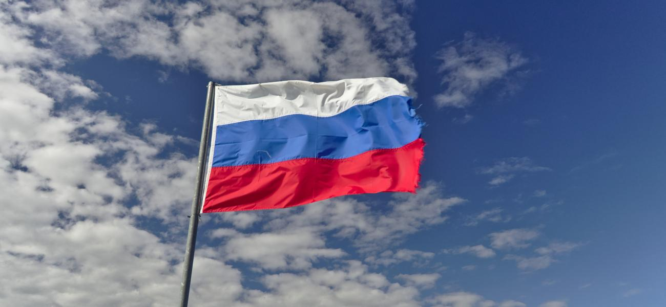 Russian flag, a little raggedy, against backdrop of blue sky and clouds.