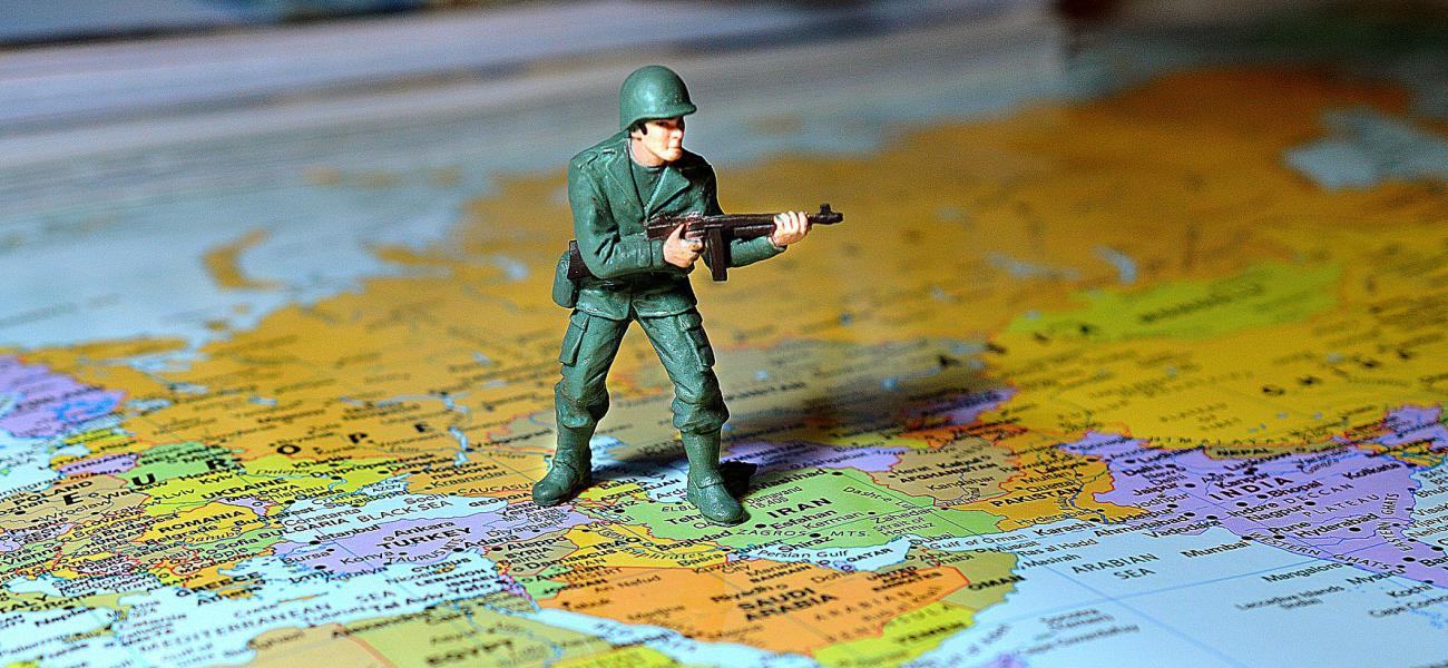 Toy soldier standing on a map of the Middle East, Iran, Israel, Syria.