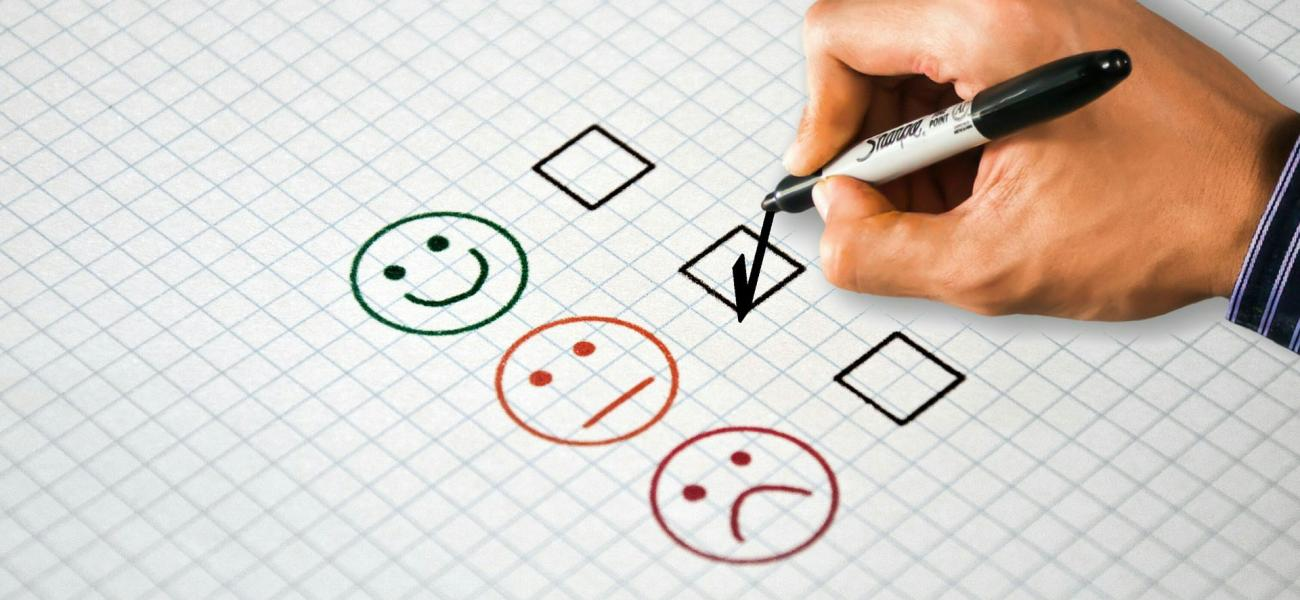 A poll with a happy face, neutral face and a sad face where someone is checking off the box next to the neutral face.